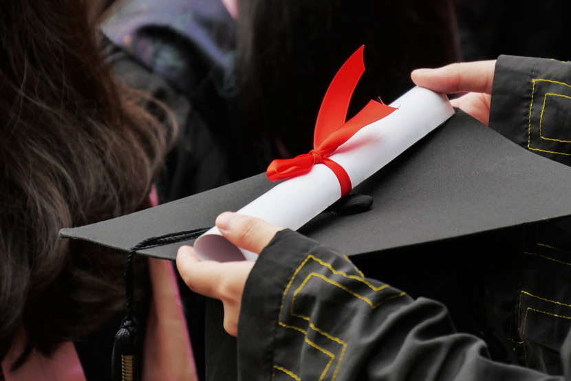 A university graduate holds their certificate during a graduation ceremony in Guangzhou, Guangdong province, May 26, 2019. Li Zhihao/VCG