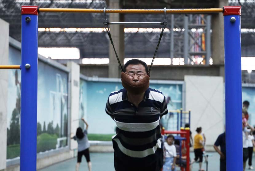 A man performs an exercise that is capable of alleviating the symptoms of cervical spondylosis in Shenyang, Liaoning province, July 11, 2019. IC