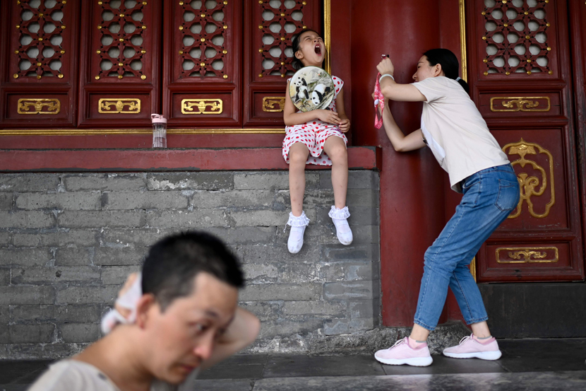 A girl holding a fan yawns while posing for a photo at a park in Beijing, July 22, 2019. The Beijing weather department issued a blue warning on July 22, indicating a heat wave for the coming days. Wang Zhao/AFP/VCG