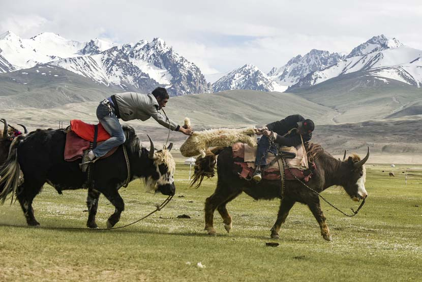 Two Kazakh men scramble for a sheep during a traditional horseback game in Taxkorgan County, Xinjiang Uygur Autonomous Region, July 9, 2019. Zhang Hui/VCG