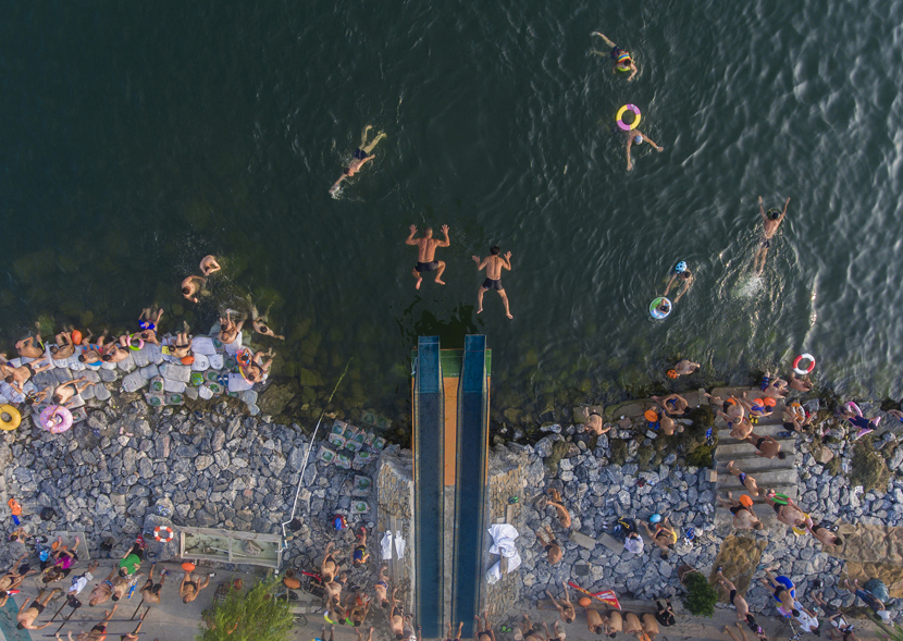 An aerial view of swimmers diving into the Han River to escape the summer heat in Xiangyang, Hubei province, July 22, 2019. Yang Dong/VCG