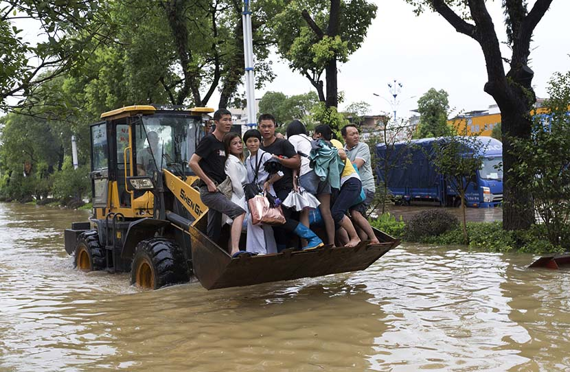 A bulldozer transfers people trapped by rising waters from the Lijiang River in Guilin, Guangxi Zhuang Autonomous Region, July 13, 2019. Hu Peng/VCG