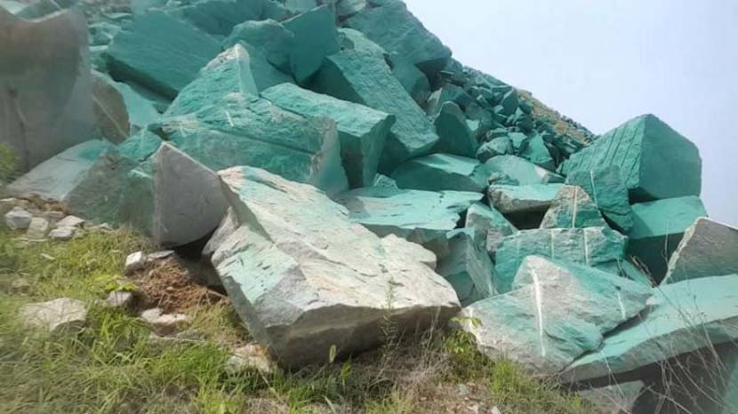 Rocks outside a stone processing plant are shown painted green in Xintai, Shandong province, 2019. @齐鲁网 on Weibo