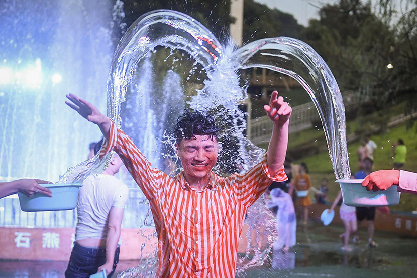 A man is doused with water during a community event in Changsha, Hunan province, July 31, 2019. Yang Huafeng/CNS/VCG