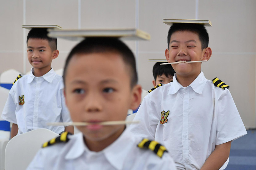Children practice proper manners and posture at a space-themed summer camp in Kunming, Yunnan province, Aug. 1, 2019. Ren Dong/CNS/VCG