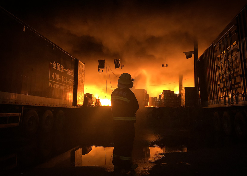 A firefighter watches on as a fire burns in a logistics center in Guangzhou, Guangdong province, July 30, 2019. VCG