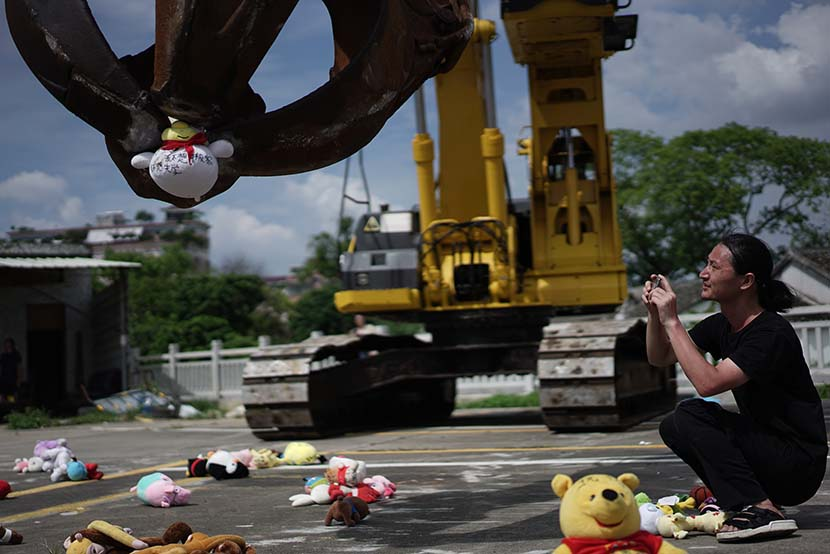 Chinese artist Nut Brother photographs an excavator picking up a doll during the performance of his art installation in Shenzhen, Guangdong province, Aug. 4, 2019. Qiu Rong for Sixth Tone