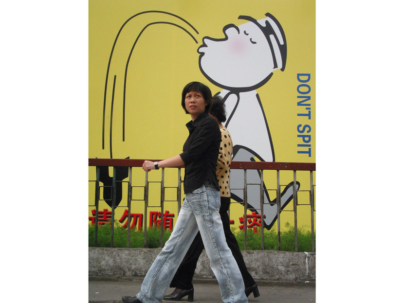 Two people walk past a wall warning against spitting in public, Shanghai, 2003. VCG