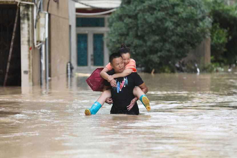 A man carries a woman through floodwaters caused by Typhoon Lekima in Dajing Town in Yueqing, Zhejiang province, Aug. 10, 2019. Lekima made landfall in Zhejiang early Saturday morning. Zhejiang Daily/IC