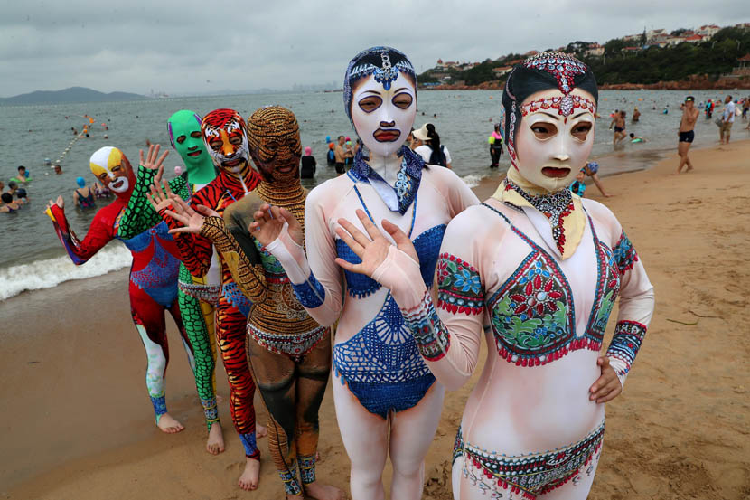 "Models wearing colorful, full-body ""facekinis"" pose for photos on a beach in Qingdao, Shandong province, Aug. 5, 2019. Xu Chongde/VCG"