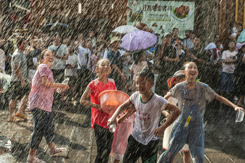 Children play under falling water during a water-sprinkling festival celebrated in Enshi, Hubei province, Aug. 9, 2019. Zhou Ahan/VCG