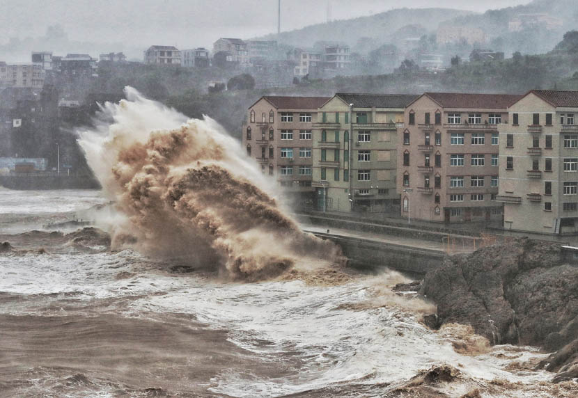 Large waves crash against a sea wall in front of a row of residential buildings in Taizhou, Zhejiang province, Aug. 9, 2019. China issued a red alert ahead of Typhoon Lekima making landfall in Zhejiang province. VCG