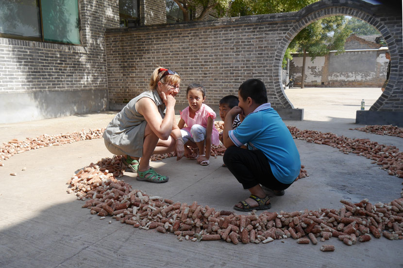 An international artist talks to local children as part of an art project in Xu Village, Heshun County, Shanxi province, 2015. Courtesy of Qu Yan