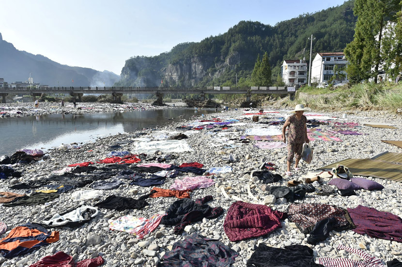 Villagers lay their clothes, sheets, and blankets along the stony banks of a river to dry after floodwaters caused by Typhoon Lekima receded in Xianju County, Taizhou, Zhejiang province, Aug. 12, 2019. Zhejiang Daily/VCG