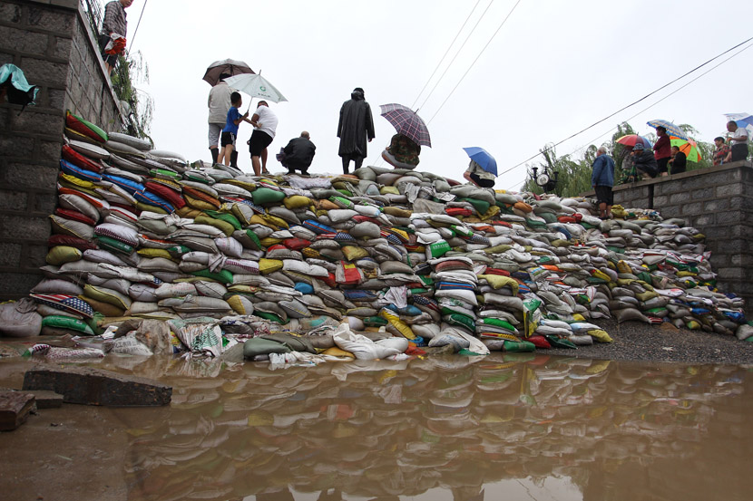 People stand on sandbags piled high to stop the flow of floodwaters caused by Typhoon Lekima in Zhangqiu District, Jinan, Shandong province, Aug. 13, 2019. VCG