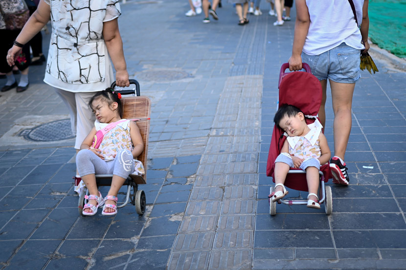 Two women pull their sleeping children in strollers as they walk along a road in Beijing, Aug. 13, 2019. Wang Zhao/AFP/VCG