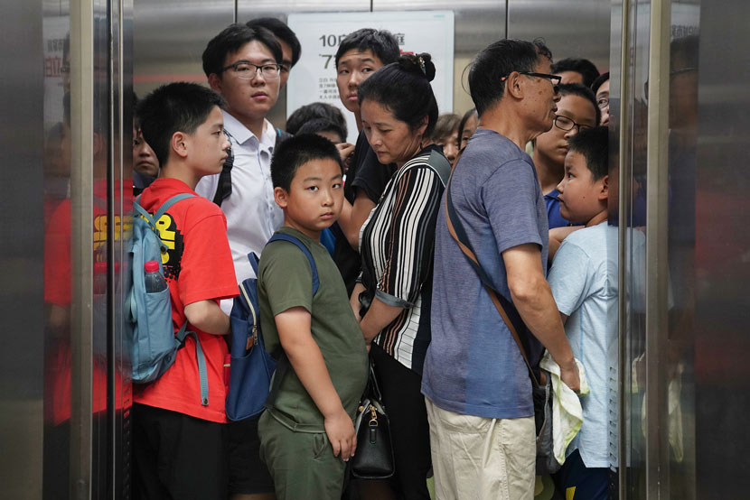 "Students and their family members crowd an elevator in what's been called the ""tutor tower"" to attend extracurricular classes in Beijing, July 15, 2019. Cai Yingli/Caixin/VCG"