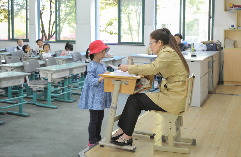 A girl talks to a teacher during an interview for a private school's enrollment in Hangzhou, Zhejiang province, April 15, 2017. VCG