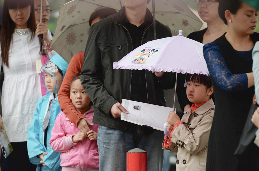 Children and their parents wait for face-to-face interviews for a private school's enrollment in Shanghai, May 10, 2014. IC