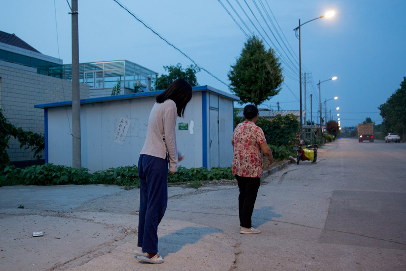 Zhao Yangyang and her grandmother stand on a road in front of their house in Sheyang, Jiangsu province, July 29, 2019. Shi Yangkun/Sixth Tone