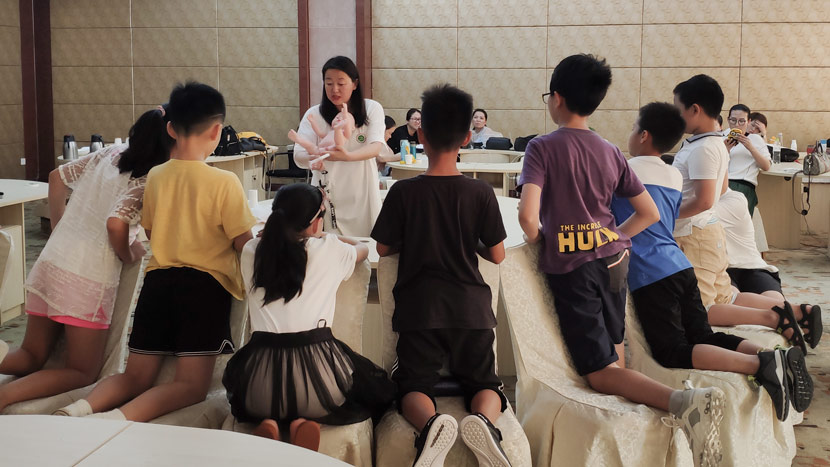 Sex education lecturer Wang Yi shows children how to use a tampon on a doll during a sex education summer camp in Qingdao, Shandong province, Aug. 4, 2019. Fan Yiying/Sixth Tone