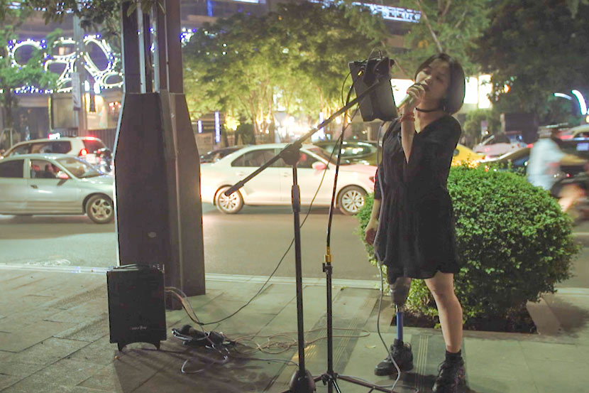 Xie Renci sings into a microphone on a sidewalk in Chongqing, May 20, 2017. Lü Xiao/Sixth Tone