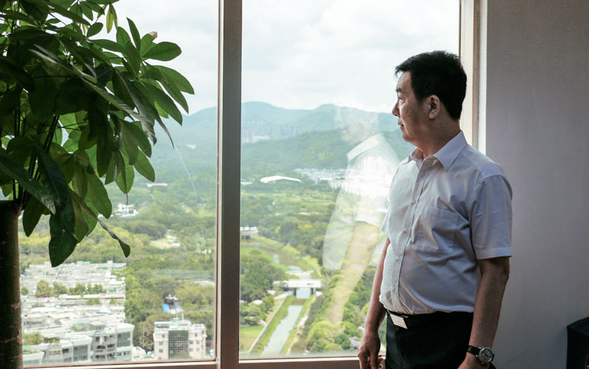 Lin Feng looks out the window of his office in Shenzhen, Guangdong province, June 9, 2017. Cai Yiwen/Sixth Tone