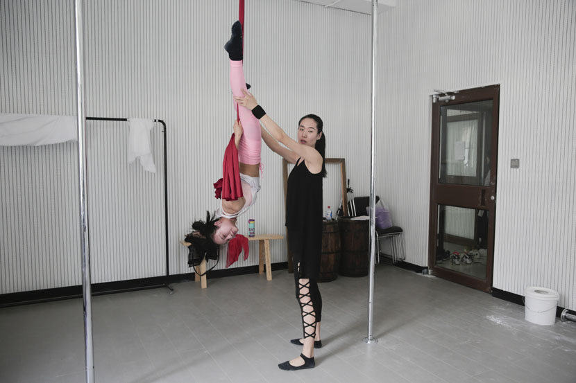 Pole dancing coach Meng Yifan (right) guides dancer Chen Dandan's movements as Chen hangs upside down at a studio in Tianjin, June 3, 2017. Chen Ronghui/Sixth Tone