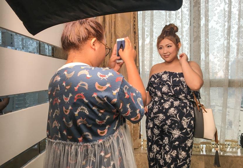 Plus-size modeling agent Huang Fei (left) takes sample photos of model hopeful Wang Jialin in Guangzhou, Guangdong province, June 20, 2017. Fan Yiying/Sixth Tone
