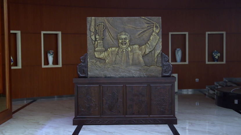 A screenshot showing a relief sculpture of Fuyao CEO Cao Dewang. From Douban. Cao is depicted holding an entrepreneurship award and the Chinese flag.