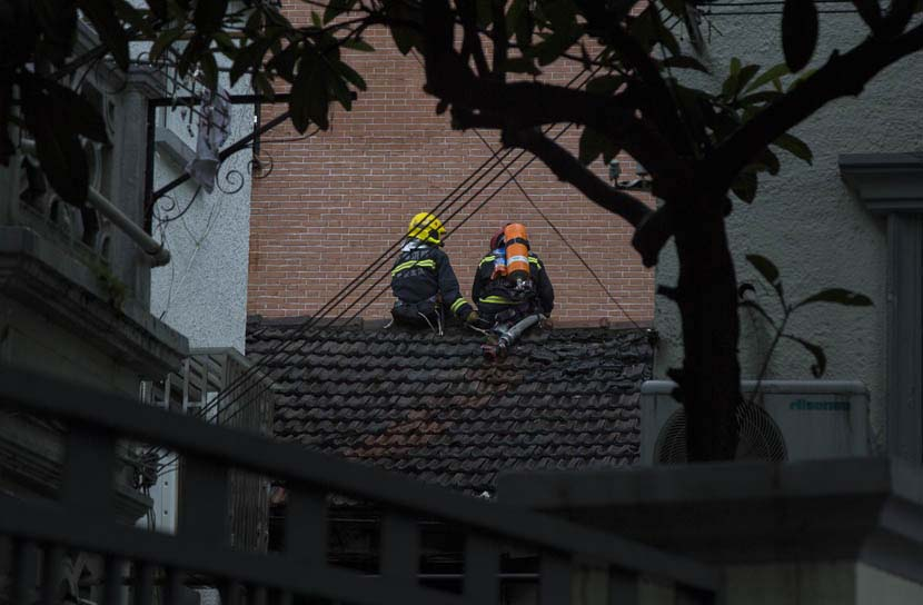 Two firemen take a break after extinguishing a blaze at a clothing store warehouse in central Shanghai, Sept. 6, 2019. Shi Yangkun/Sixth Tone