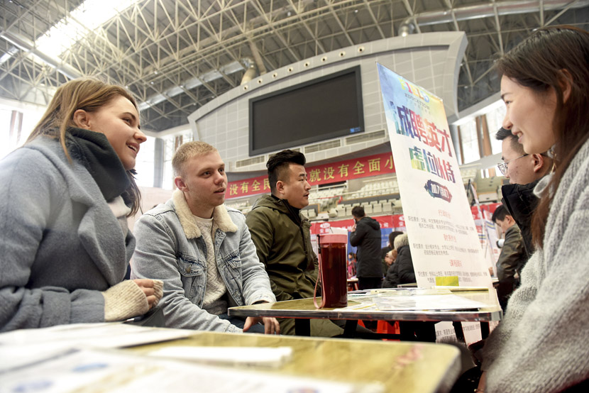 Staff at a training center talk to people at a job fair in Huainan, Anhui province, Feb. 23, 2019. Chen Bin/VCG