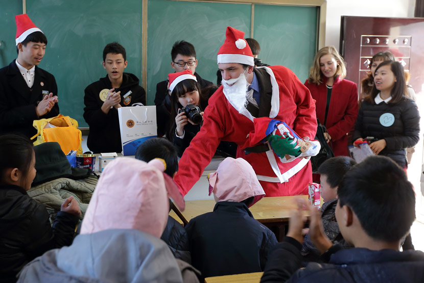 A foreign teacher dresses up as Santa Claus for a Christmas-themed lesson at an international school in Zhuji, Zhejiang province, Dec. 23, 2014. Luo Shanxin/IC
