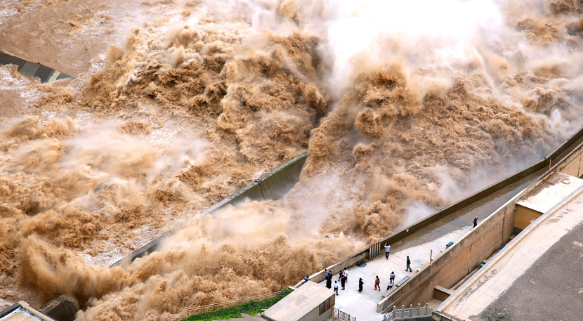 People watch the water released by the Sanmenxia Dam, constructed to prevent floods in Sanmenxia, Henan Province, Aug. 28, 2019. Sun Meng/IC
