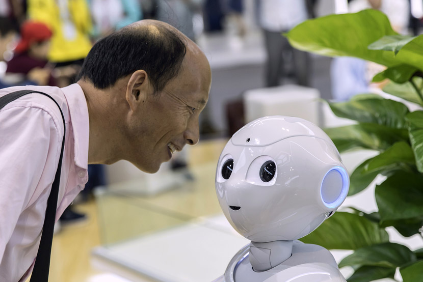 An attendee looks at a semi-humanoid robot at the World Artificial Intelligence Conference (WAIC) in Shanghai, Aug. 29, 2019. Qilai Shen/Bloomberg/VCG