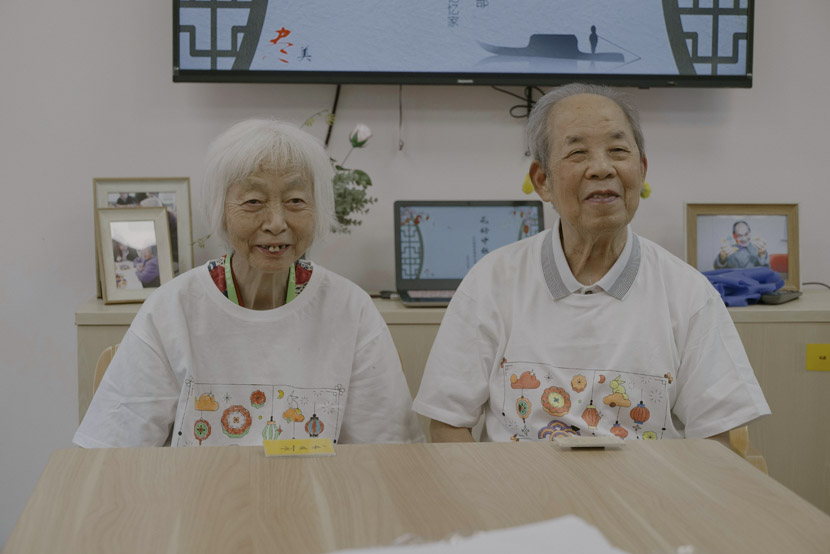Dementia patients Liu Yunshu (left) and Yu Jinliang (right) wear the T-shirts they made at the event in Shanghai, Sept. 12, 2019. Zhu Yuqing/Sixth Tone