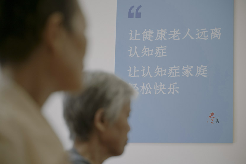 "A poster on the wall of the events room reads, ""Help healthy old people stay away from dementia; help the dementia families find relaxation and happiness."" Photo taken in Shanghai, Sept. 17, 2019. Zhu Yuqing/Sixth Tone"