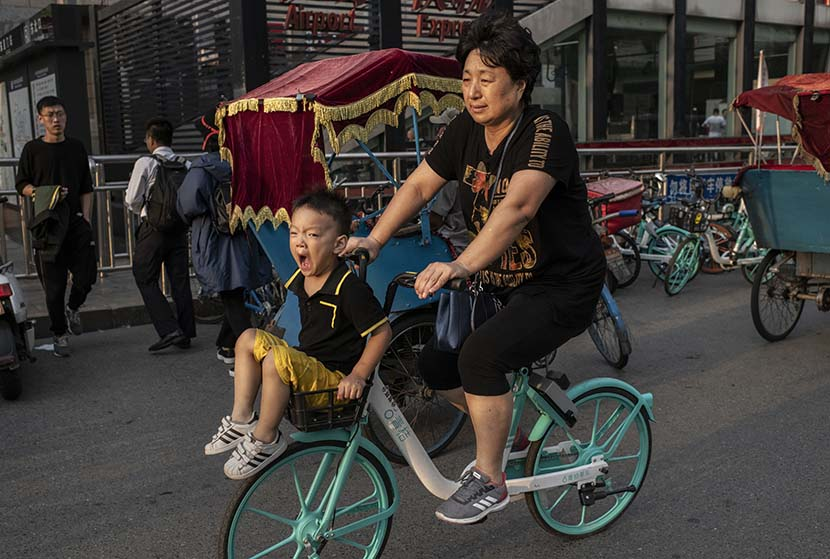 A young boy yawns as he's pedaled through rush hour in Beijing, Sept. 20, 2019. Kevin Frayer/Getty Images/VCG