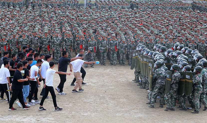 Freshmen students at Nantong Vocational College show off their riot response skills at the conclusion of their mandatory military training in Nantong, Jiangsu province, Sept. 20, 2019. Xu Peiqin/VCG