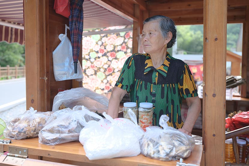 A woman waits for customers at her souvenir booth inside Qianjiangyuan National Park in Zhejiang province, July 18, 2019. Zhou Pinglang for Sixth Tone