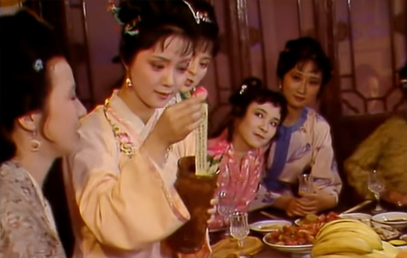 "A screenshot from the 1987 TV series ""Dream of the Red Chamber"" shows Xue Baochai picking a peony-related poem out of a vase. From CCTV电视剧 on YouTube"