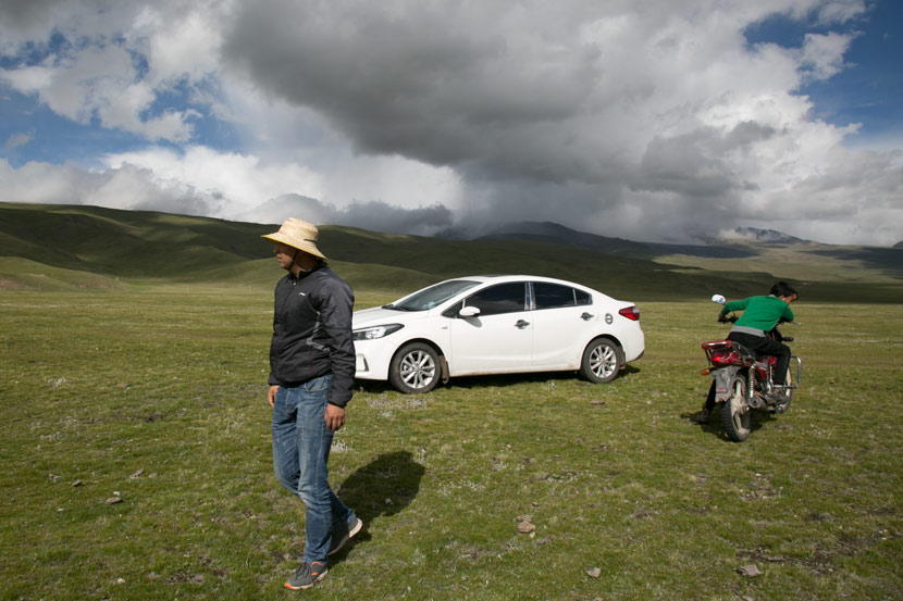 Ma Jingui (left) and his son drive their cattle and sheep to their winter pastures in Qilian County, Qinghai province, July 2019. Shi Yangkun/Sixth Tone