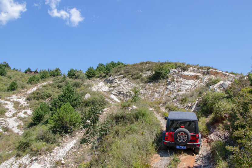 Wang Long drives up a steep trail outside of Beijing, Aug. 30, 2019. Kenrick Davis/Sixth Tone