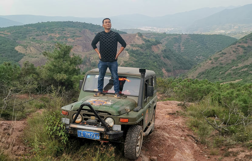 "Gao Chunyan poses for a photo on the hood of his ""Beijing Jeep"" in a rural area in Yunnan province, Sept. 25, 2019. Courtesy of Gao Chunyan"