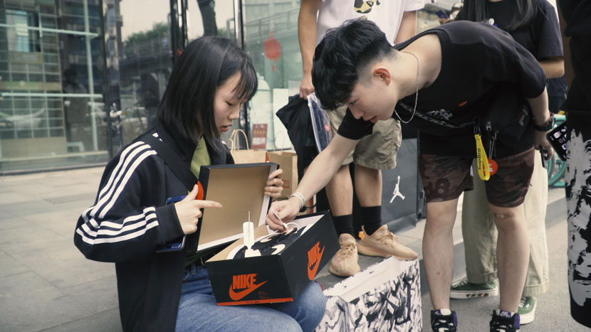 A man checks the label of a pair of sneakers in Chengdu, Sichuan province, May 2019. Sun Zhichao for Sixth Tone
