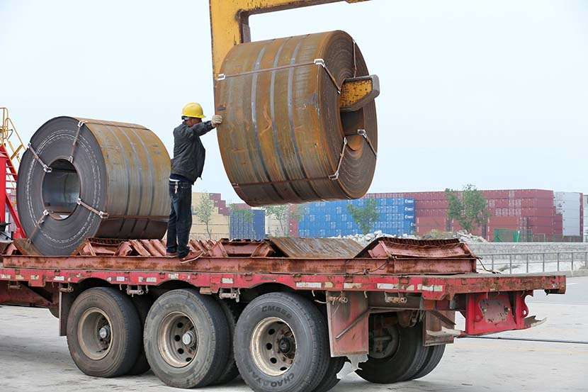 A worker uploads industrial-size steel rolls from a trailer in Qidong, Jiangsu province, May 19, 2018. Such cargo is too heavy for some bridges with load-bearing restrictions. IC
