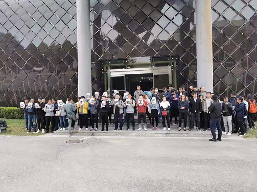 Current and former employees of solar energy firm Hanergy Thin Film Power Group Limited stand in front of the company's headquarters during a three-day protest over unpaid wages. From The Paper