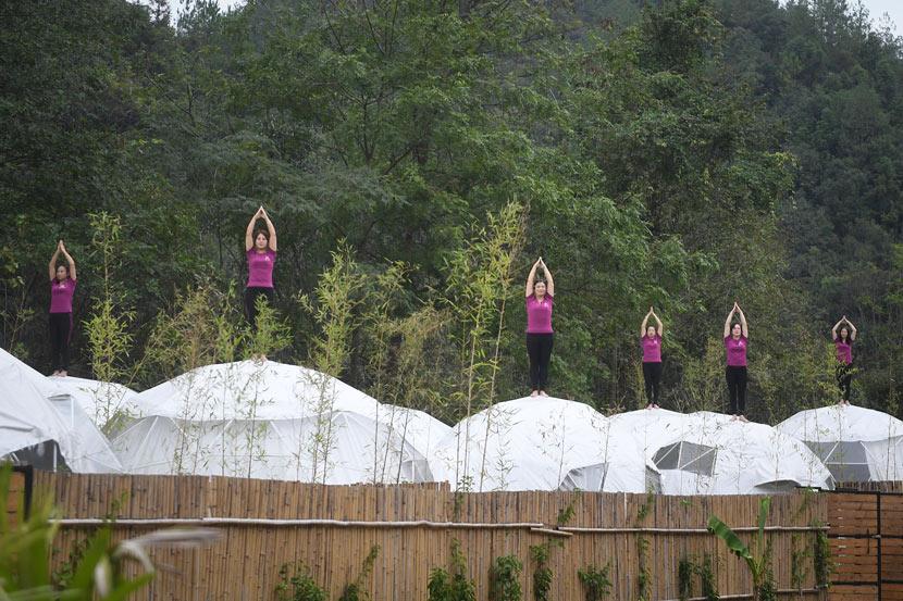 Women participate in a yoga show atop safari tents at Donghuzhai Scenic Area in Jiujiang, Jiangxi province, Oct. 15, 2019. VCG