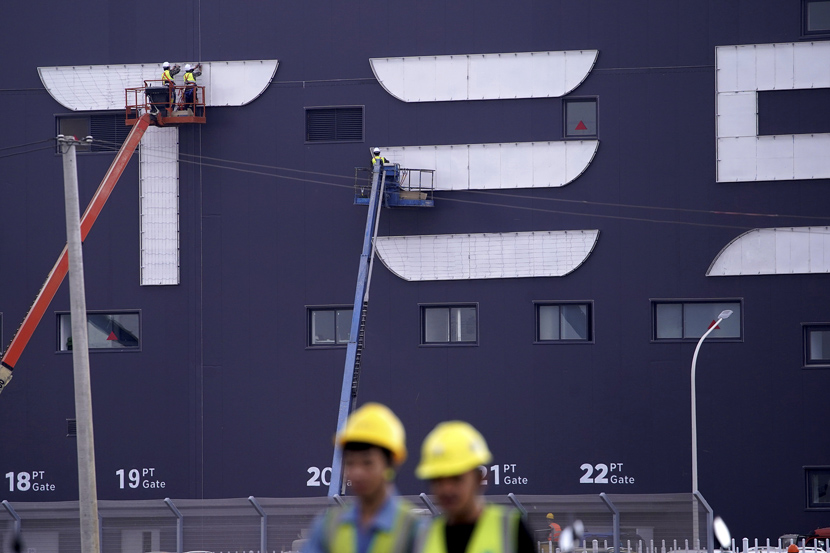 Workers on cranes install the logo for Tesla Gigafactory 3 at the Lingang Area in Shanghai, Oct. 18, 2019. Tesla Gigafactory 3 is expected to begin production at the end of 2019. Aly Song/Reuters/VCG