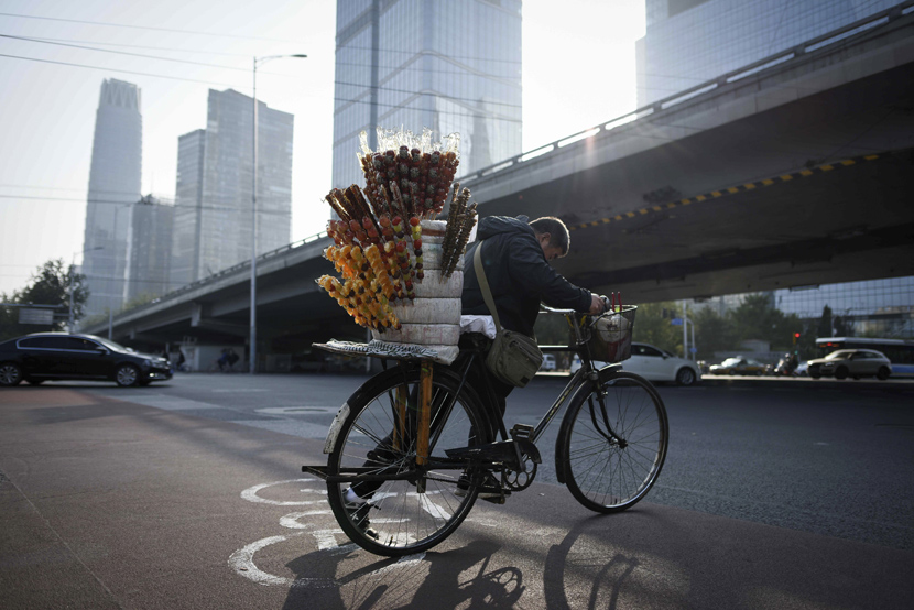 A vendor rides his bicycle across a street in Beijing's central business district, Oct. 18, 2019. Wang Zhao/AFP/VCG